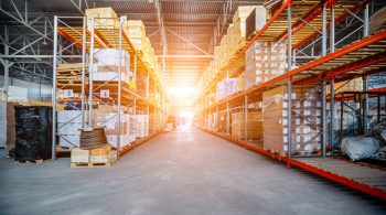 Warehouse industrial and logistics companies. Long shelves with a variety of boxes and containers. Bright sunlight.